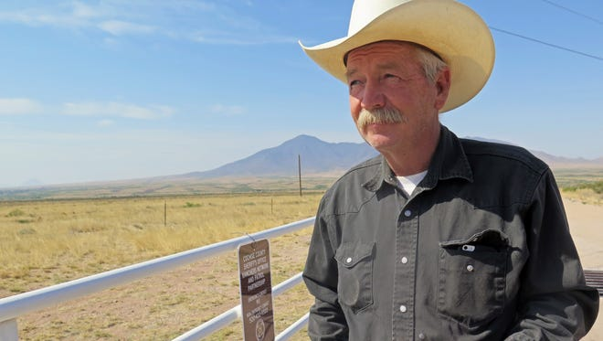 Cattle rancher John Ladd holds his new radio issued by the Cochise County Sheriff's Department for use in cases of emergency near Naco, Ariz., about 10 miles of it sits on the international border on Thursday, June 9, 2016. Ladd says drug smugglers frequently cross through his land and have burglarized his home on several occasions. The radios were handed out to about 30 border ranchers so they could have faster communication with 911 dispatchers.