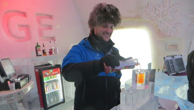 A bartender pours a drink at Hotel de Glace in Quebec, Canada.