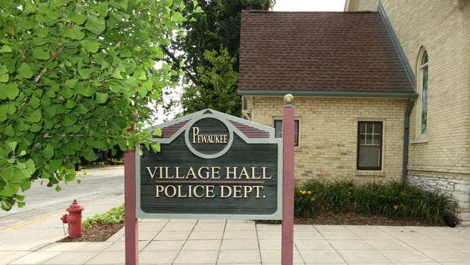 A sign directs people to Pewaukee Village Hall.