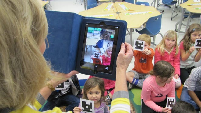 First grade teacher Diane Marshall uses an iPad to record answers that students give using Plicker cards.