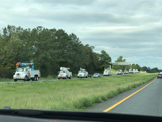 Utility trucks stream into Tallahassee on I-10.