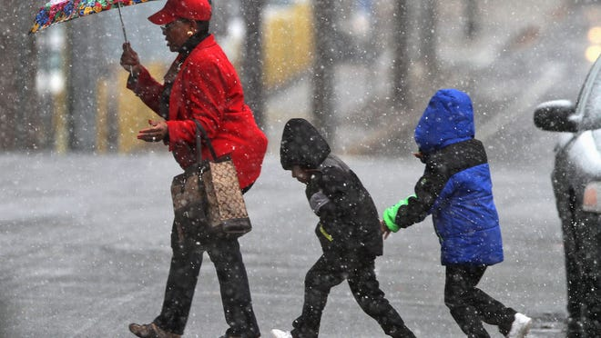 Snow falls as a woman and children cross a street in New Brunswick on Wednesday.