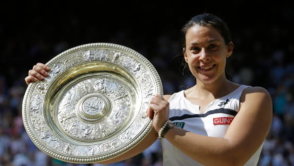 FILE - In this July 6, 2013, file photo Marion Bartoli, of France, smiles as she holds the trophy after winning the women's singles final match against Sabine Lisicki of Germany at the All England Lawn Tennis Championships in Wimbledon, London. Bartoli says she is coming out of retirement and returning to the tennis tour next season. The 33-year-old Frenchwoman made the announcement via a Twitter post on Tuesday, Dec. 19, 2017. (AP Photo/Anja Niedringhaus, File)