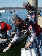 Trey Wurst (front) releases their catch of fish back into the fishery as his fishing partner Thomas Hubbard looks on Feb. 19 at the Lake Hartwell Early Bird Open on Lake Hartwell at Green Pond Landing.