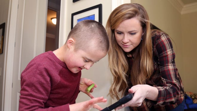 Hillsboro Middle School sixth-grader Ryan Williams, who has Down syndrome, uses an iPad app to help communicate with his baby sitter, Maddie Garcia, at his home in Franklin.