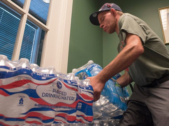 Jimmy Crowley stacks donated water. He stored the donations