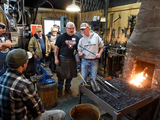 Ken Zitur works with veterans near a coal-fired forge