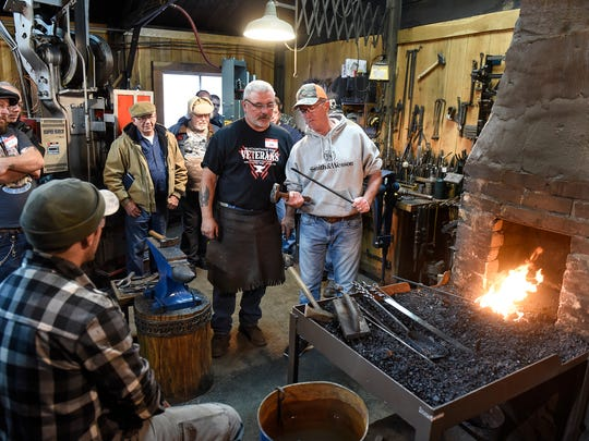 Ken Zitur works with veterans near a coal-fired forge during a Blacksmithing for Veterans event Friday, Nov. 10 at Ken's Custom Iron near Avon.