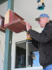 Bob Manzke securely fastens a repaired bird feeder to a post on the couple's porch.