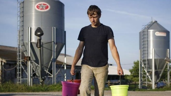 Curtis Coombs carries buckets of milk while feeding Holstein calves at his family's dairy farm in Smithfield, Kentucky.