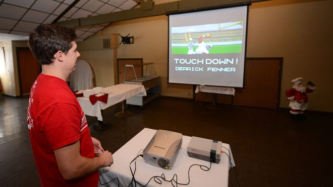 Nathan Smithson, organizer for the Tecmo Tundra Bowl II at the Watering Hole in Howard, works the Nintendo controller. He will set up eight or nine stations the night before, testing all the equipment and copies of the game.