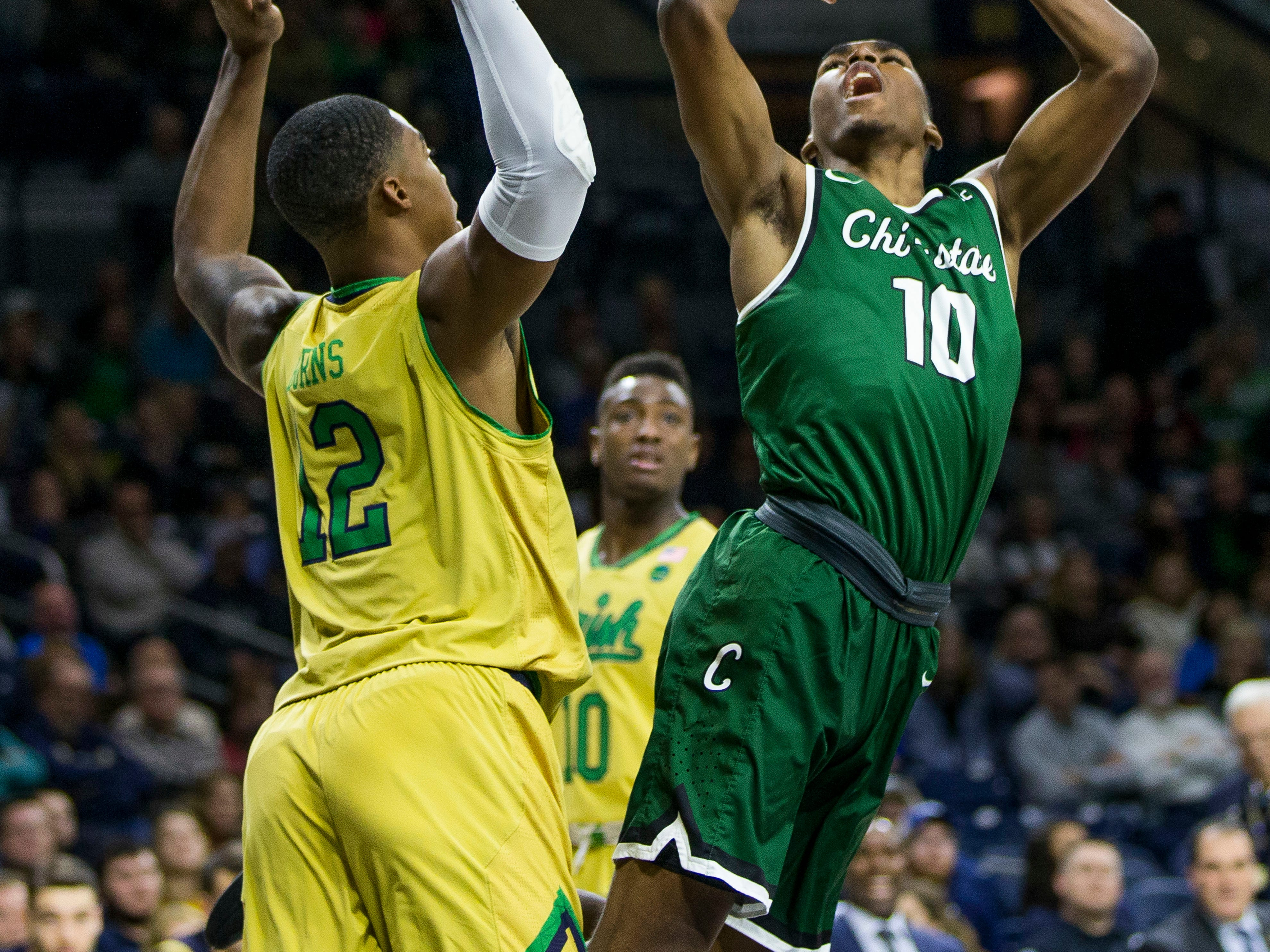 Chicago State's Anthony Harris (10) goes up to shoot in front of Notre Dame's Elijah Burns (12) during the first half of an NCAA college basketball game Thursday, Nov. 16, 2017, in South Bend, Ind. (AP Photo/Robert Franklin)