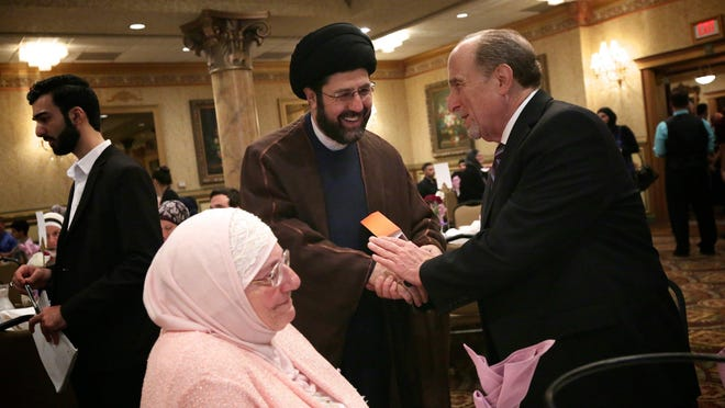 Imam Hassan Al-Qazwini reaches out to Ramsey Makled of Dearborn during a Ramadan dinner at the Bint center in Dearborn in July.