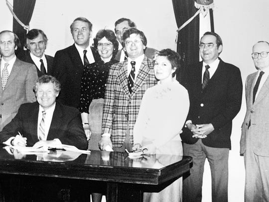 The late Harry Behney, at right in a dark jacket, photographed April 17, 1981 as Gov. Richard Snelling signs the captive insurance law.  From left to right behind the governor are Dean Rowden, Vermont Bankers Assoc.; Chris Barbieri, Vt. Chamber; Gar Anderson, Hospitality and Travel Assoc.;  Rep. John Farmer; Sen. Peter Welch; Link Miller, Lobbyist; George Chaffee, Commissioner, Banking and Insurance; Rep. Ann Just; Rep. Stu Hunt, Chair House Commerce; Rep. John Zampieri, Chair House Transportation; Rep. Susan Auld; Harry Behney, Secretary, Agency of Development and Community Affairs; Rep. Peter Giuliani, Chair House Ways and Means.