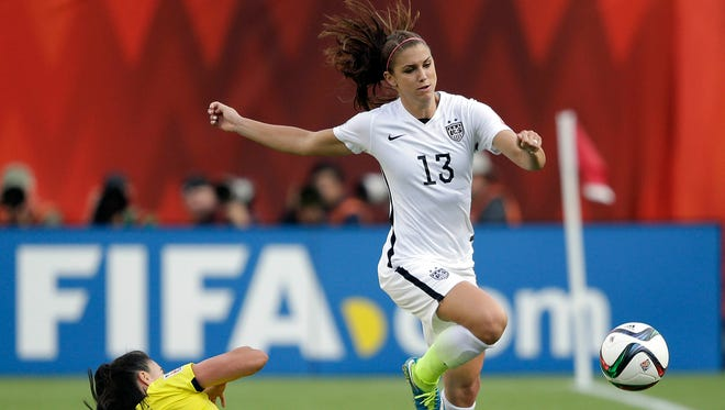 United States forward Alex Morgan (13) and Colombia defender Nataly Arias (14) go for the ball during the second half in the round of sixteen in the FIFA 2015 women's World Cup soccer tournament at Commonwealth Stadium.