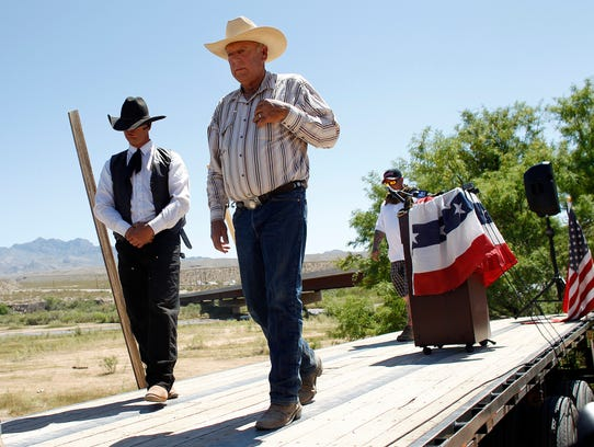 Rancher Cliven Bundy, center, walks off stage after speaking at a news conference near Bunkerville, Nev., Thursday, April 24, 2014. Bundy, a Nevada rancher who became a conservative folk hero for standing up to the government in a fight over grazing rights, lost some of his staunch defenders Thursday after wondering aloud whether blacks might have had it better under slavery. (AP Photo/Las Vegas Review-Journal, John Locher)