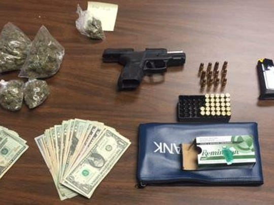 Police released this photo Thursday of drugs, an illegal gun and suspected drug proceeds they say were seized from a man on probation after a traffic violation.