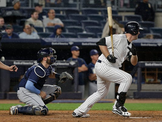New York Yankees Brian McCann follows through on a base hit down the left field line as Tampa Bay Rays catcher Curt Casali watches during the sixth inning of a baseball game Friday, April 22, 2016, in New York. Carlos Beltran scored on the play. (AP Photo/Julie Jacobson)