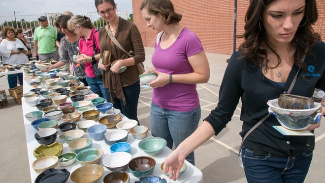 Stevie Lopez of Las Cruces, right, and others browse the colorful selection off dishes during last year's Empty Bowls annual fundraising event for El Caldito Soup Kitchen at St. Paul's United Methodist Church.