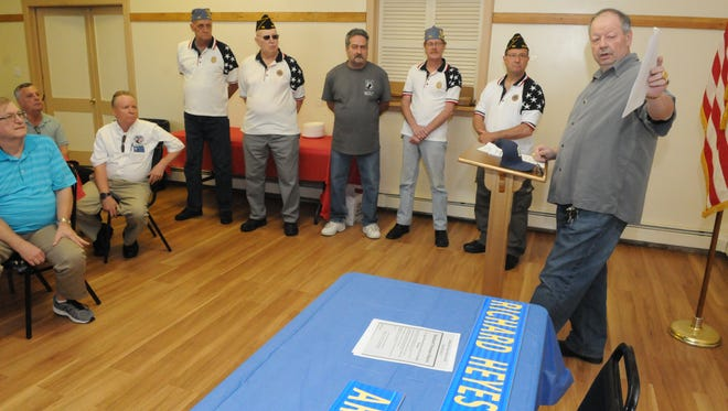 In this May 28, 2016 file photo, Belleville Township Councilman Kevin Kennedy, right, holds up a document detailing the accomplishments of five veterans who died in combat, and who will have streets named in their honor.