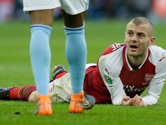 Arsenal's Jack Wilshere looks up as he lies on the ground following a tackle during the English League Cup Final between Arsenal and Manchester City at Wembley stadium in London, Sunday, Feb. 25, 2018.(AP Photo/Tim Ireland)