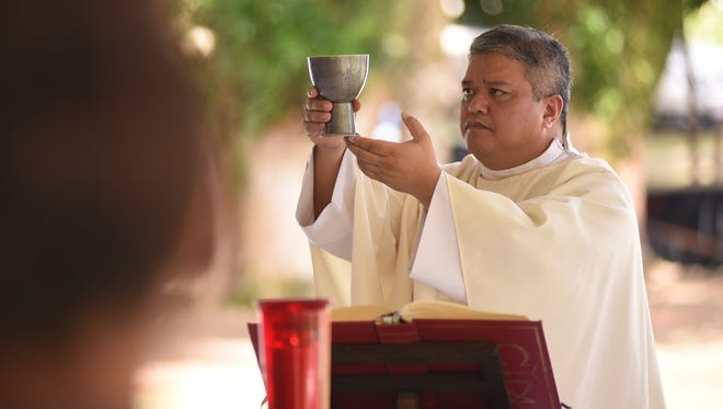 Father Jeff San Nicolas celebrates a memorial Mass at the Chagui'an massacre site in Yigo on Tuesday, Aug. 8, 2017. During the recapture of the northern part of Guam by American soldiers from Japanese Imperial armed forces in World War II, U.S. Marines discovered a Japanese truck loaded with the bodies of decapitated Chamorro men. A further search of the area after the gruesome discovery, resulted in the finding 21 men, remaining in a kneeling position with their hands bound behind their backs and all beheaded. The ceremony was held to remember 45 killed in the tragic massacre.