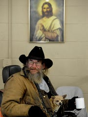 Cowboy Luttrell and his dog Jack, 19, have a cup of coffee to warm up while they for wait for a hot meal at Catholic Charities on Wednesday.