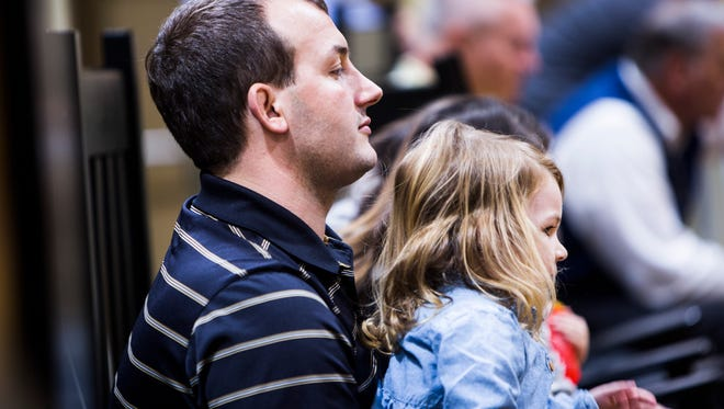 Anderson University associate AD Matthew Finley watches the Anderson University versus Coker basketball game recently with his daughter, Charlotte Grace.