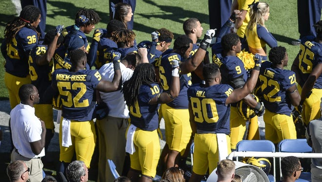 Some Michigan players raise their fists during the national anthem Saturday before the game against Wisconsin.