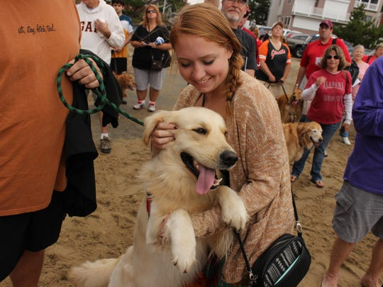 Annapolis, Maryland resident Alexis Ring gives her dog Merlin a scratch behind the ears before the blessing of the animals at the second annual Golden Jubilee.