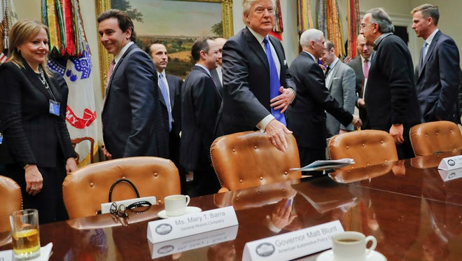 President Donald Trump tosses his folder on the table before the start of a meeting with automobile leaders in the Roosevelt Room of the White House in Washington, Tuesday, Jan. 24, 2017. From left are, GM CEO Mary Barra, Ford Motors CEO Mark Fields, the president and Fiat Chrysler Automobiles CEO and Sergio Marchionne.  (AP Photo/Pablo Martinez Monsivais)