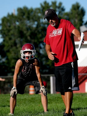 Head coach John Novara instructs the running backs on proper routes for blocking on plays during the first day of football practice Monday, August 8, 2016, at Portland High School in Portland, Mi.