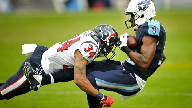 Titans wide receiver Tre McBride (16) is tackled by Texans cornerback A.J. Bouye (34) in the fourth quarter at Nissan Stadium Sunday Dec. 27, 2015, in Nashville, Tenn.
