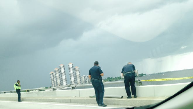 Fort Myers police officers assess the damage to a rail on the southbound lane of the Caloosahatchee Bridge after a small trailer went over the side.