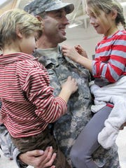 Newly promoted Maj. Beau Biden shows his insignia to his children, Hunter and Natalie, after a Delaware National Guard promotion ceremony at the Smyrna Readiness Center attended by his father, Vice President Joe Biden.