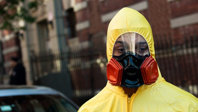 Hopes that the Ebola scare could be abating faded with reports that a New York doctor had been hospitalized with the virus. Here, a young man wearing biohazard gear stands on a corner in New York City.