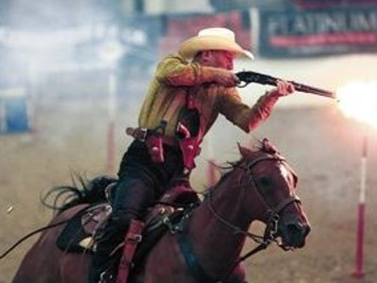 A rider competing in cowboy mounted shooting fires