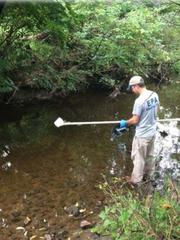 An EPA technician samples water from a creek near Hockessin.