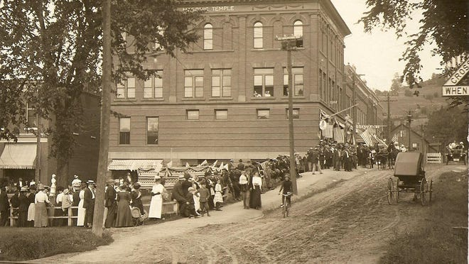 A crowd on upper Bridge Street awaits a summer parade in the 1910s.