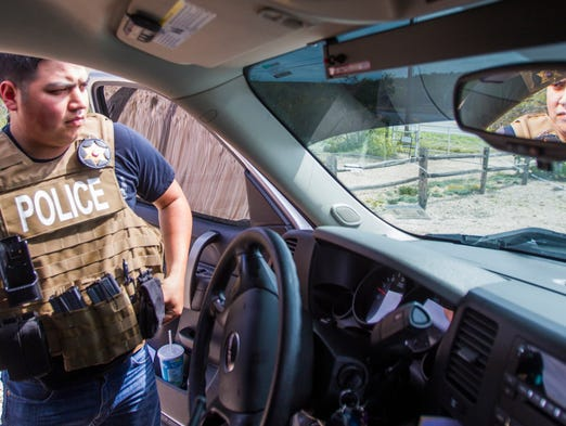 """Starr County High-Intensity Drug Trafficking Area task force investigator Nat Gonzalez puts his vest on while looking for a possible """"load vehicle"""" in Garciasville, Texas, on March 5, 2014. The joint task force was formed to combat illegal drugs along the border."""