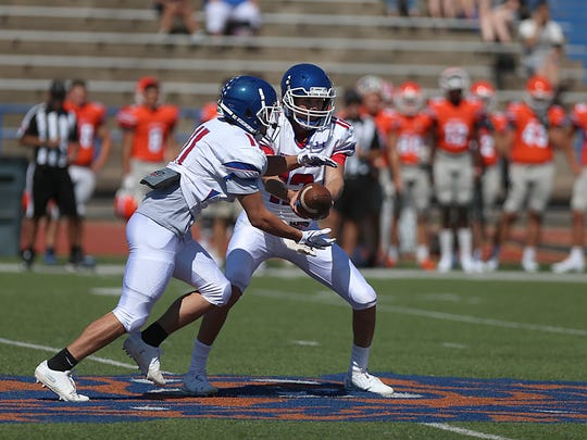 Cooper's Aidan Thompson (12) hands the ball to running back Nic Bailey (11) during the Cougars' scrimmage against the San Angelo Central Bobcats on Friday at San Angelo Stadium.