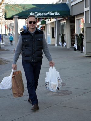 Dan Kendle, of Alexandria, Va., finishes up his holiday shopping in Rehoboth Beach on Saturday.