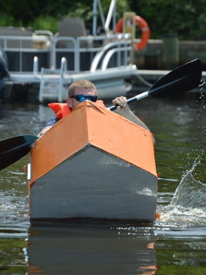 """Craig Whitaker, of Seaford, tries to hang on as his cardboard boat """"Tuna Dreams"""" buckles. The boat sank."""