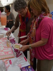 """Debbie Guy and Karla Acuna cut a cake for visitors during the 6th annual """"Paint Pink for Breast Cancer"""" event at St. Frances Cabrini hospital. (Sept. 30, 2016)"""