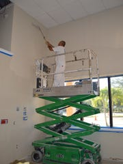 Pedro Ornelas reaches a high spot on the Habitat ReStore wall thanks to the help of a scissor lift.
