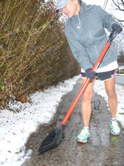 Yishane Lee of Ridgewood shoveling away the slushy snow that she knew would turn icy when the temperature dropped later that night. Children take this route to school, and she doesn't want them slipping and getting hurt.