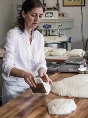 Mahasti Vafaie shapes dough into bread at Flour Head