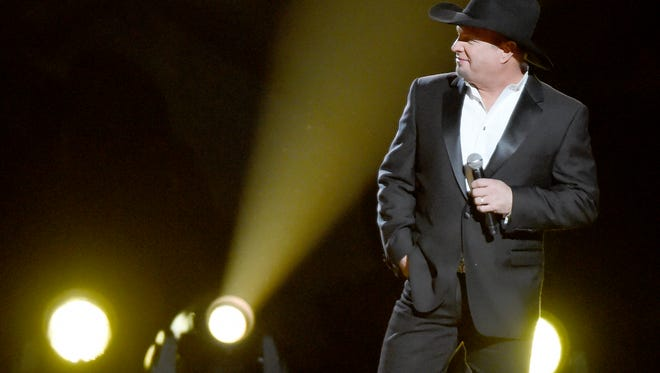 Garth Brooks smiles as he performs with his wife Trisha Yearwood at the 2016 CMA Awards  Wednesday, Nov. 2, 2016, in Nashville, Tenn.