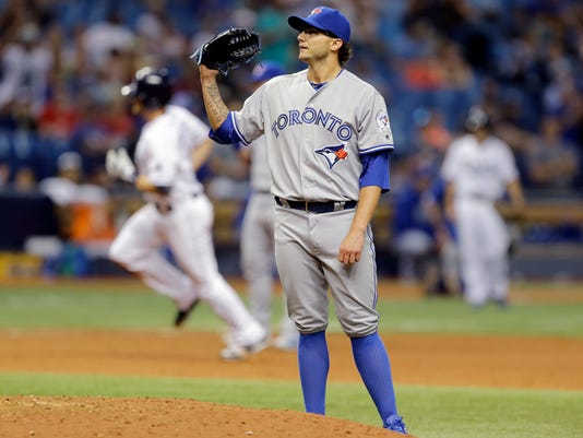 Toronto Blue Jays relief pitcher Brett Cecil gets a new baseball as Tampa Bay Rays' Logan Forsythe runs around the bases after hitting a two-run home run during the ninth inning of a baseball game Tuesday, April 5, 2016, in St. Petersburg, Fla. The Rays won 3-2. (AP Photo/Chris O'Meara)