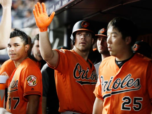 """FILE - In this June 10, 2017 file photo, Baltimore Orioles' Chris Davis, center, celebrates with teammates after hitting a home run during a baseball game against the New York Yankees in New York. Davis went on the 10-day disabled list Tuesday with a right oblique strain, and it will likely be after the All-Star break before he's ready to swing a bat in a big league game again. """"I think three weeks would be real ambitious,"""" manager Buck Showalter said Saturday. """"I'd sign up for that right now."""" (AP Photo/Frank Franklin II, File)"""